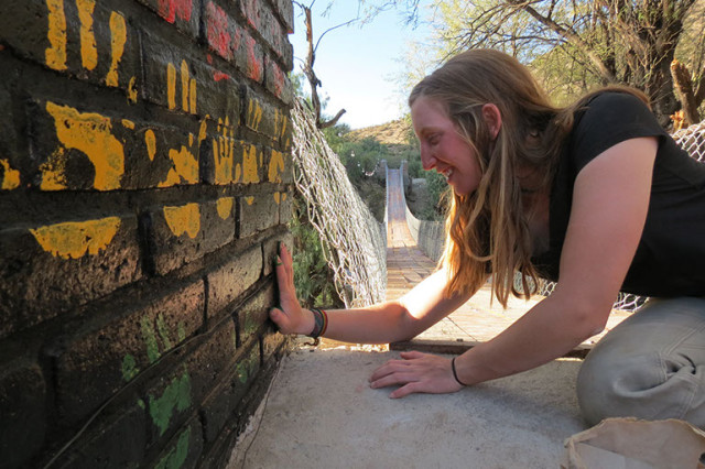 Nathalie DeNey of Cornell University's Engineers Without Borders adds her handprint to the bridge foundation her team built in Bolivia. (Image courtesy of Cornell University)