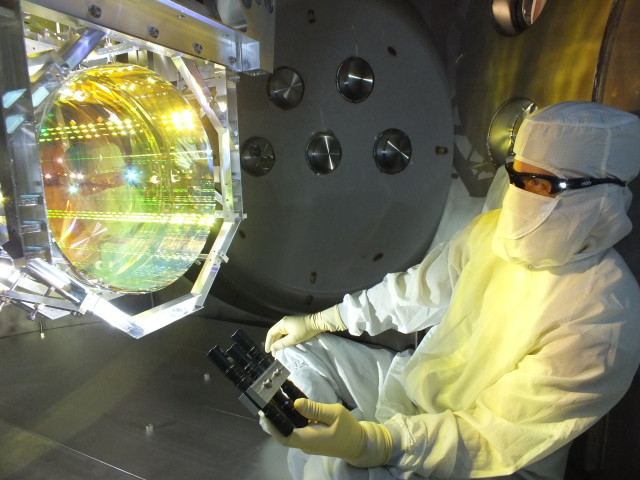 A LIGO optics technician inspects one of LIGO's core optics by illuminating its surface with light at a glancing angle. (Image Courtesy of LIGO Laboratory)