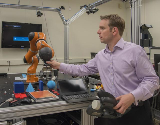 NIST engineer Jeremy Marvel adjusts a robotic arm used to study human-robot interactions. According to a NIST economic study on advanced robotics and automation—one of four reports on advanced manufacturing—Marvel's work is the type of research needed to fortify and facilitate this emerging field. (Image courtesy of Fran Webber/NIST.)