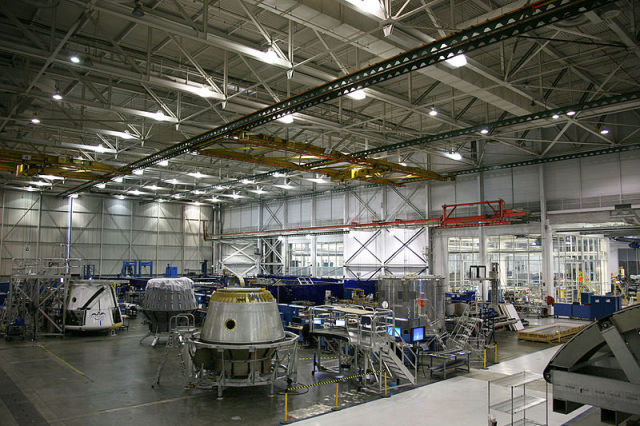 Three Dragon spacecraft, the test article used in the parachute drop test and two vehicles being prepared for flight, sit together on the production floor at SpaceX Headquarters, a 550,000 square foot facility in Hawthorne, Calif.