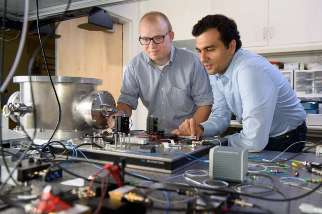 Post-doctoral scholar Peter McMahon, left, and visiting researcher Alireza Marandi examine a prototype of a new type of light-based computer. (Image courtesy of L.A. Cicero.)