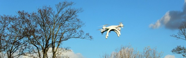 Unmanned aircraft flying above trees.