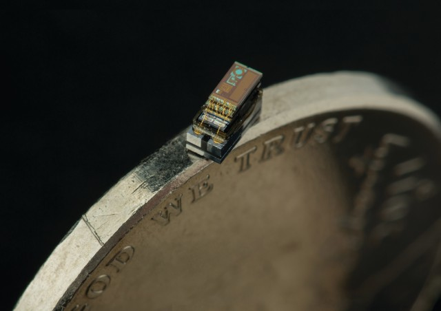 Michigan Micro Mote temperature sensor balanced on the edge of a penny. (Image courtesy of the University of Michigan.)