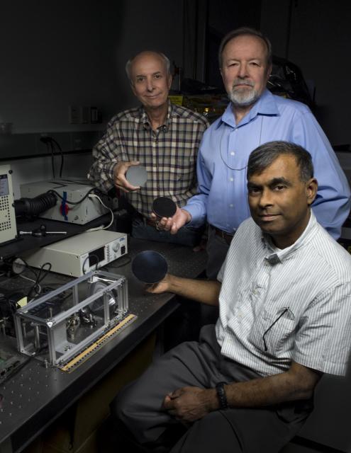 John Kolasinski, Ted Kostiuk and Tilak Hewagama hold mirrors made of carbon nanotubes in an epoxy resin. (Image courtesy of NASA/W. Hrybyk.)