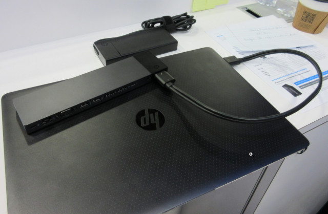 HP ZBook G3 mobile workstation at a trade show, shown with a very portable docking device (on top) and a power supply far smaller than the bricks usually found with mobile workstations.