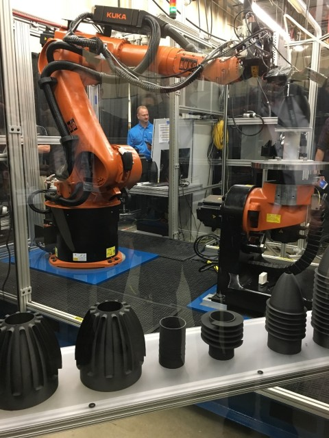 Stratasyscomposite printing head on a robotic arm has the potential of making large parts. 3D print head is being fed a filament that included chopped carbon fibers.