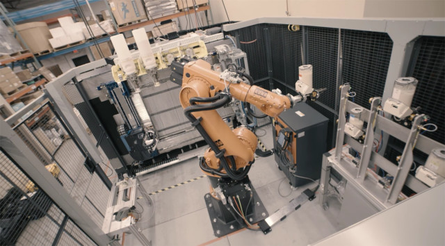 An industrial robotic arm can swap out used pellet containers or tool heads. (Image courtesy of Stratasys/YouTube.)