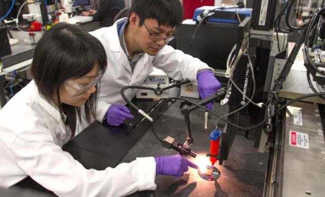 LLNL scientists Fang Qian (left) and Cheng Zhu (right) use a DIW 3D printer to print supercapacitors from graphene aerogel. (Image courtesy of Julie Russell/LLNL.)