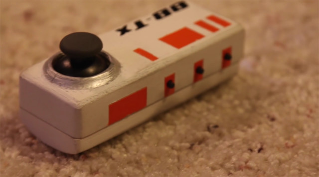 Zarick's 3D-printed remote for his BB-8 replica, with three small buttons on the side for controlling BB-8's sounds and an analog stick for controlling its motion.