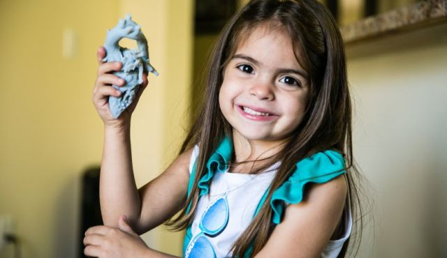 Mia holding the 3D printed model of her heart that surgeons used to visualize and plan her surgery.  Image courtesy of Stratasys.