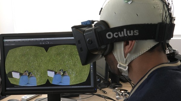 A patient in the study using an Oculus Rift to simulate walking while the EEG records brain activity. (Image courtesy of Walk Again Project).