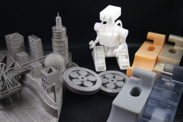 Outputs from a selection of 3D printing processes.  Clockwise, starting with robot: SLS, DLP, FDM, PolyJet, Stereolithography, Selective Laser Melting/DMLS, Electron Beam Melting.