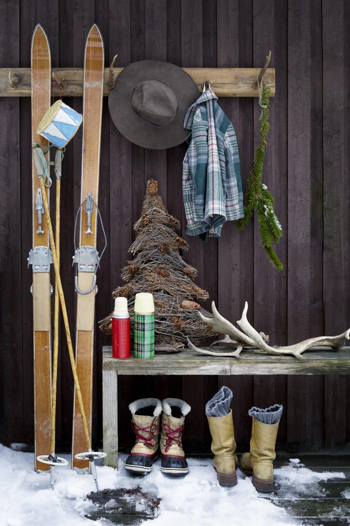 """Gör din egna vägghängare med killinghorn som fungerar som krokar, snyggast på planka av gammalt virke. Hornen är inköpta olika loppisar; ger en rustik härlig känsla på verandan. Granen gör du lätt själv med att att göra en """"granmall""""av diverse trädgrenar du sågar till. Med ståltråd sedan fäster du dit trädris och slutligen dekorerar med kottar eller annat som ger julkänsla. Passar såväl inne som ute. Rutig Barnkavaj, Fluga Barnvintage. Trummor Slow Fashion House. Sorells barnstövel. Thermosar, och gamla skidor är loppisfynd. Klassiska Frye boots."""
