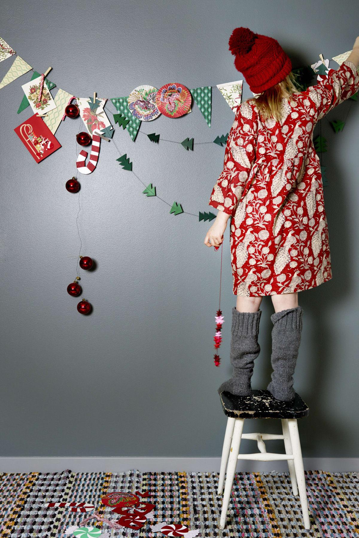 Ta vara på presentpapper och gamla julkort och gör din egna girlang att dekorera väggen med. Klipp till vimplar, varva gärna i olika storlekar också, som du lätt klipper till av fint mönstrat omslagspapper. Detta från Bungalow, 40 kr/ rullen. Klipp till små minigranar i grönt presentpapper. Julkulor som girlang gör du lätt med att trä samman med ståltråd. Ullsockar, Nordiska Ullmärken, 149 kr. Klänning, Pierrotla Lune. Agatha Dress red peacock. Mössa handstickad. Pall och trasmatta, loppisfynd.