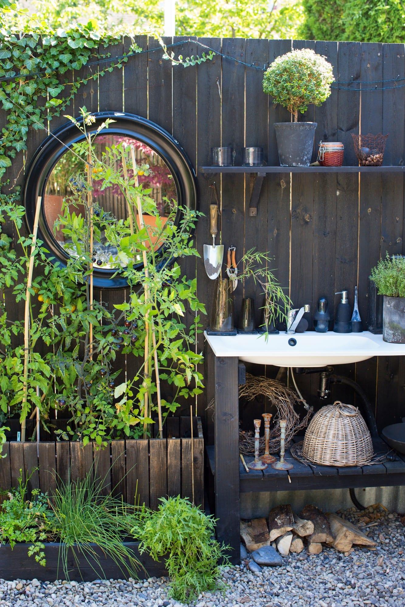 Mot det solvarma planket odlar Anders tomater, sallad och örter. Ikeavasken, där grönsakerna sköljs, fick ett hemmasnickrat underrede.