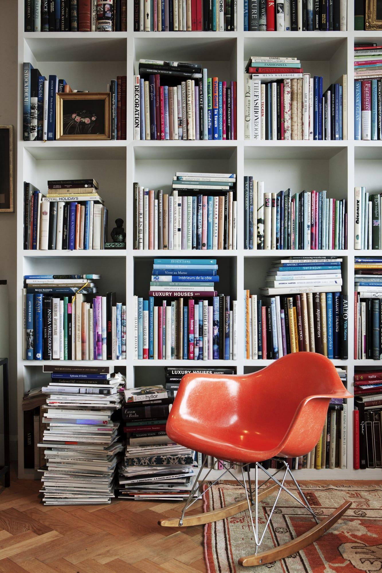 Framför tidningshögar och den platsbyggda bokhyllan står en gungstol designad av makarna Eames.