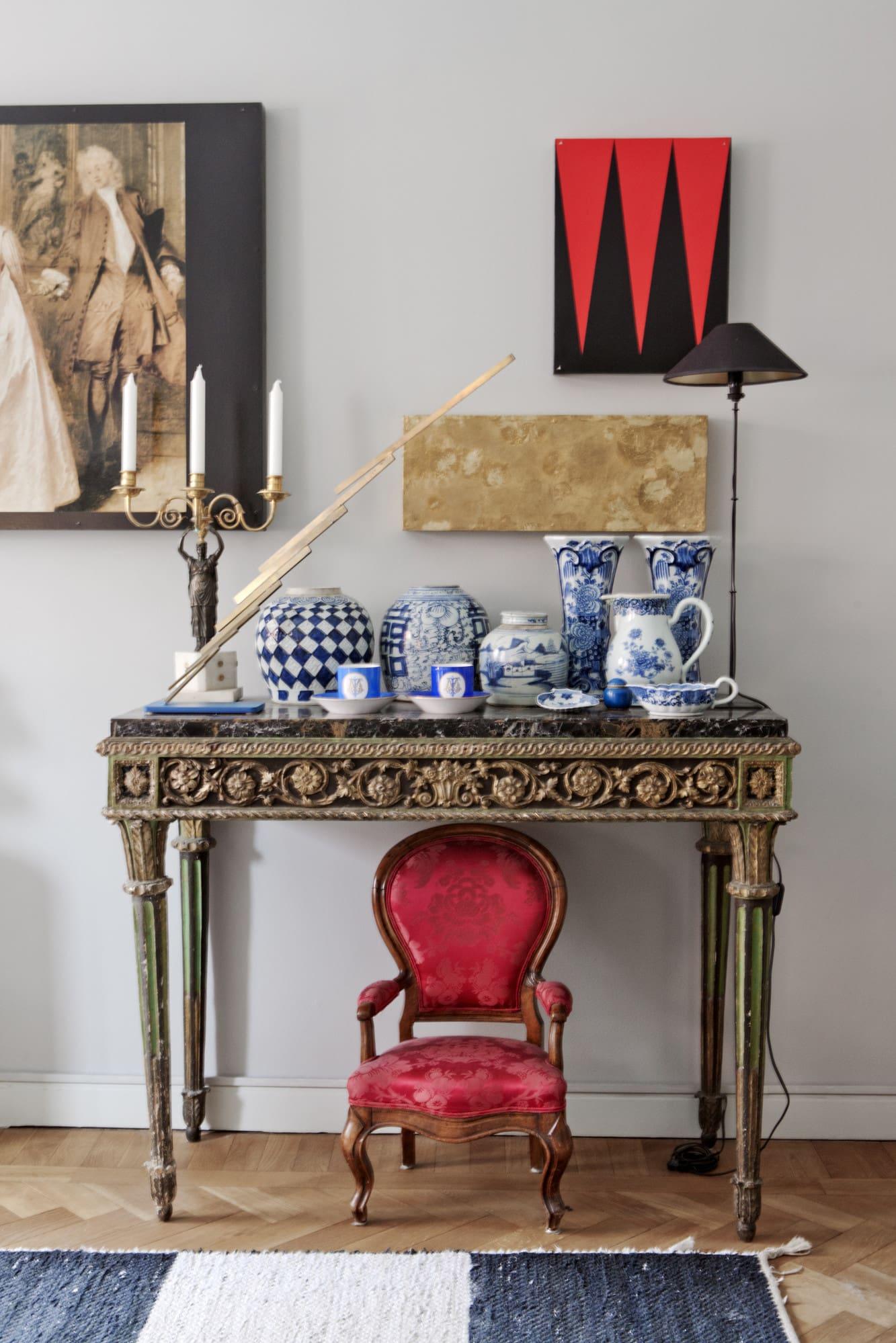 Ovanför det venetianska bordet från 1700-talet hänger en triptyk av Maya Eizin Öijer. Under står en ärvd liten barnfåtölj från 1800-talet.