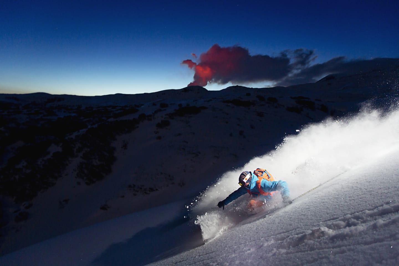 Oscar Hübinette njuter av kvällsskidåkning med Tolbatjiks röda vulkanplym ihorisonten.