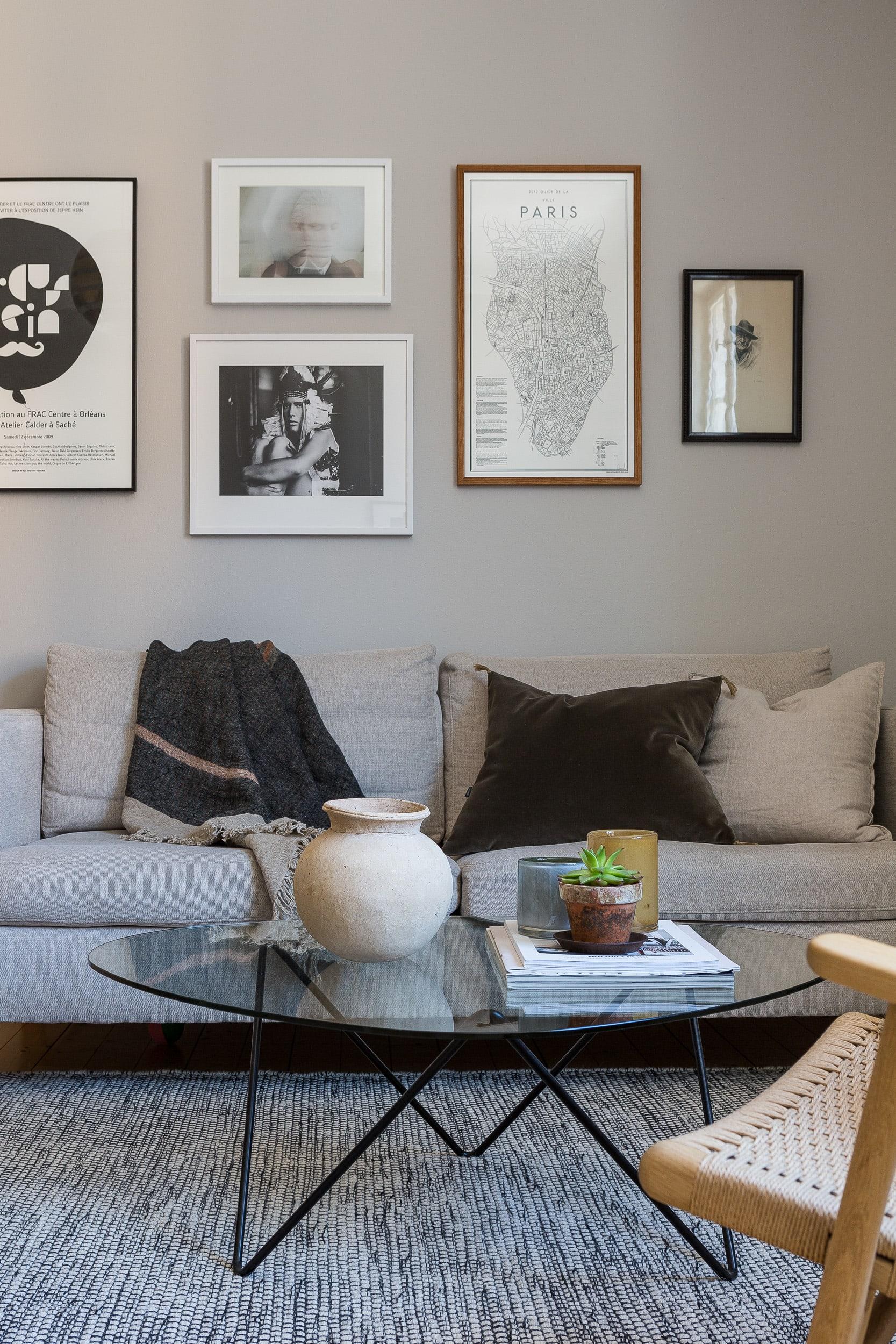 Vardagsrummet går i harmoniska milda färgtoner. Soffa Mio, soffbord Gubi, över soffan sitterolika inramade prints och en tavla köpt second hand.
