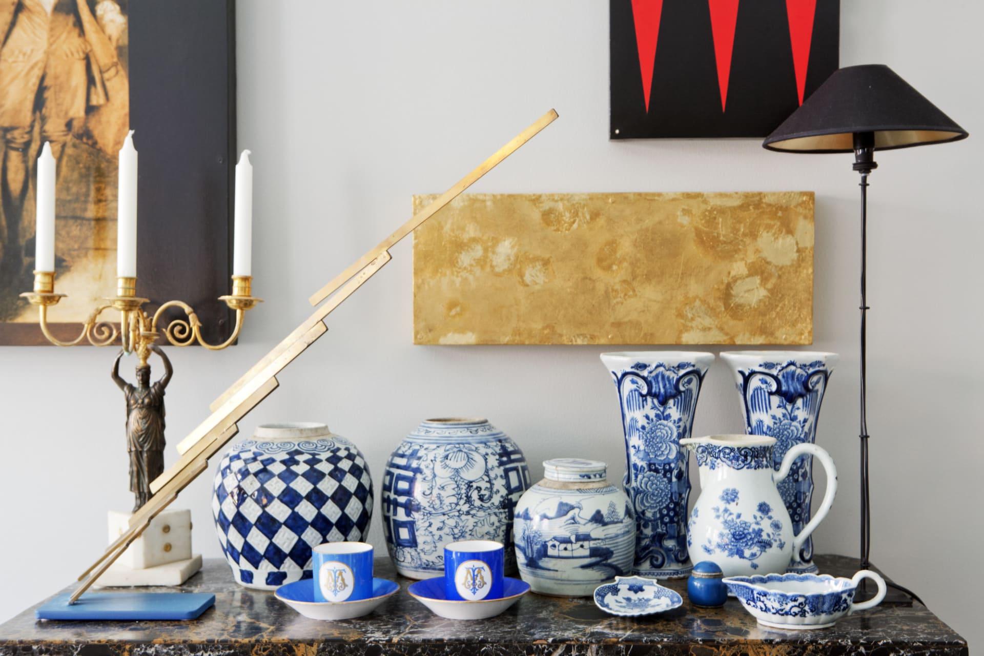 Ovanpå det venetianska bordet från 1700-talet samsas en empirljusstake i brons och marmor med en skulptur av Oscar Reutersvärd, en samling blåvitt porslin från kina och chokladkoppar. Lampan kommer från Pierre och Peters.