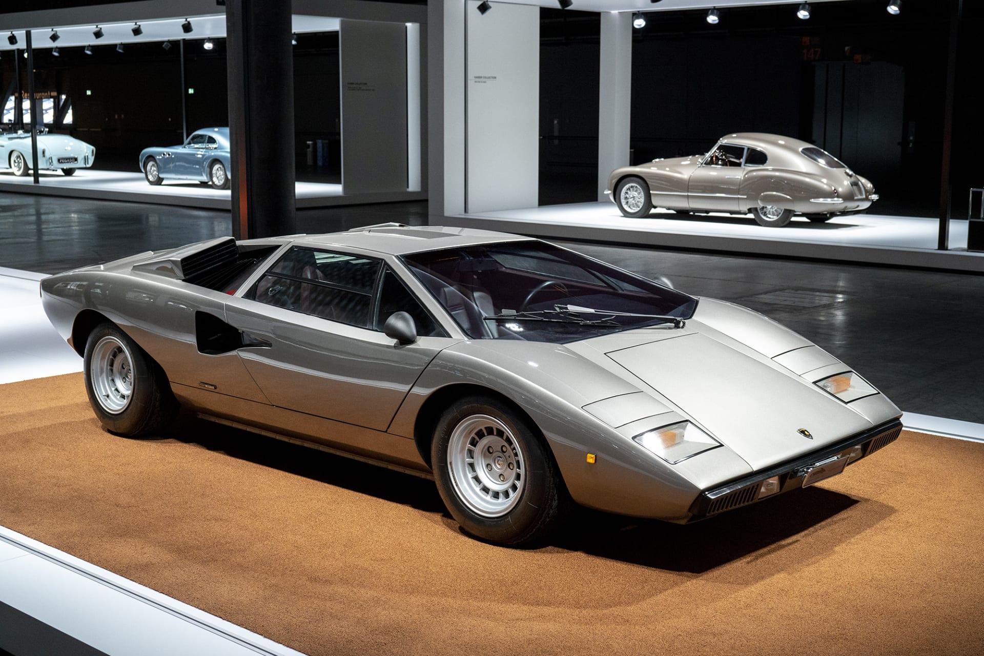 """Mästerverket och kanske världens mest kända bilikon är utan tvekan designern Marcello Gandini's Lamborghini Countach. Modellen visades upp för första gången på Geneves bilsalong 1971. Namnet uppstod då en av hantverkarna på fabriken spontant utbrast """"contacc"""" då han första gången såg bilen """"Contacc"""" är piedemontedialekt och kan fritt översättas med """"wow"""". 1974 rullade den färdiga bilen ut från fabriken och kunde redan då uppnå en hastighet på 300 kilometer i timmen tack vare sin form och den kraftfulla V12-motorn."""