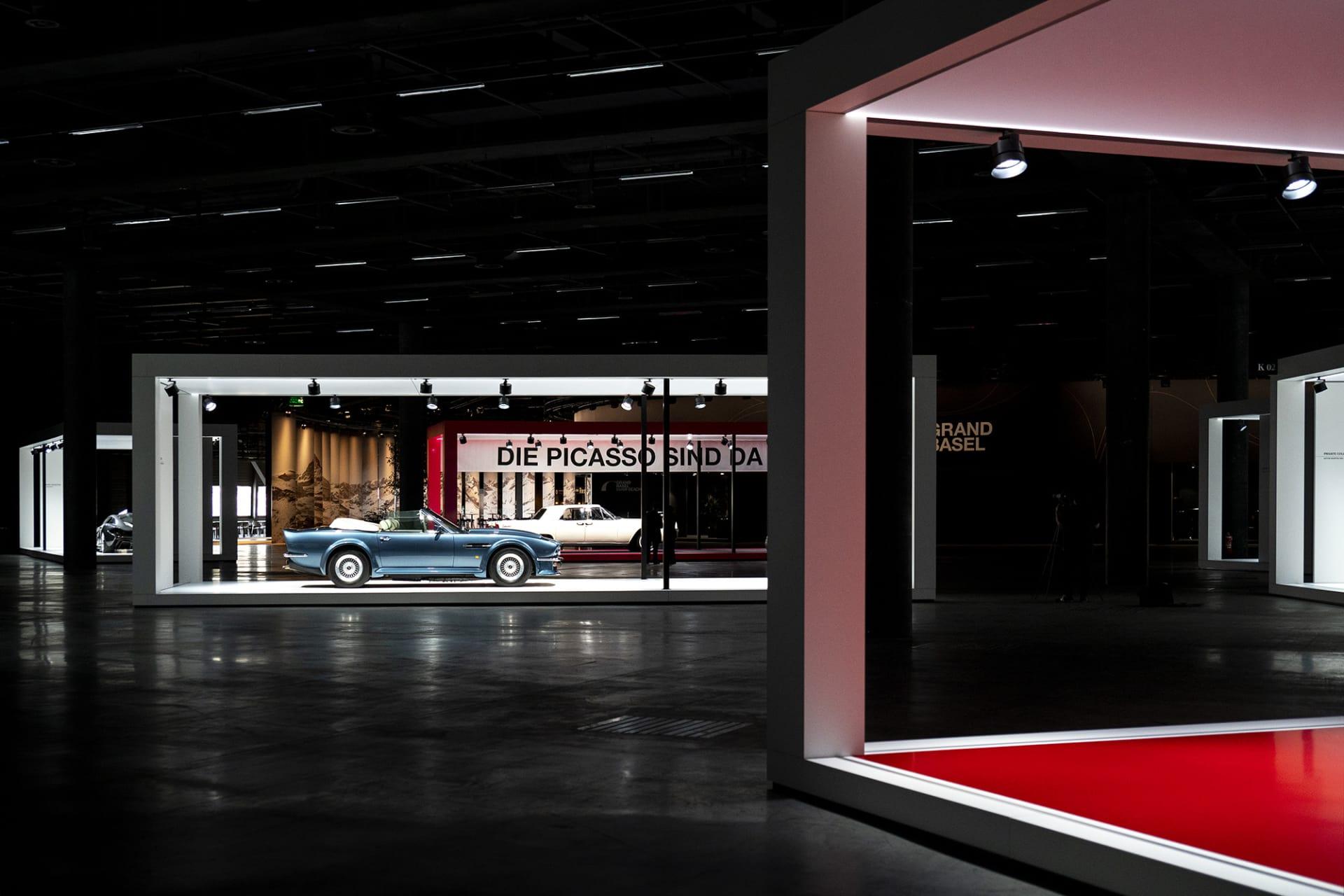 """Utformningen och ljussättningen på Grand Basel står i en helt egen klass jämfört med andra bilmässor. De speciella montrarna, som ska flytta med mässan runt om i världen, gör att bilarna ramas in på en mycket smakfullt vis. I mitten på bilden en Aston Martin V8 Vantage Volante, en bilmodell James Bond körde i filmen """"The Living Daylights"""" fast då inte som kabriolettversion. Som kabriolett byggdes endast 192 exemplar och det gör den extremt värdefull."""