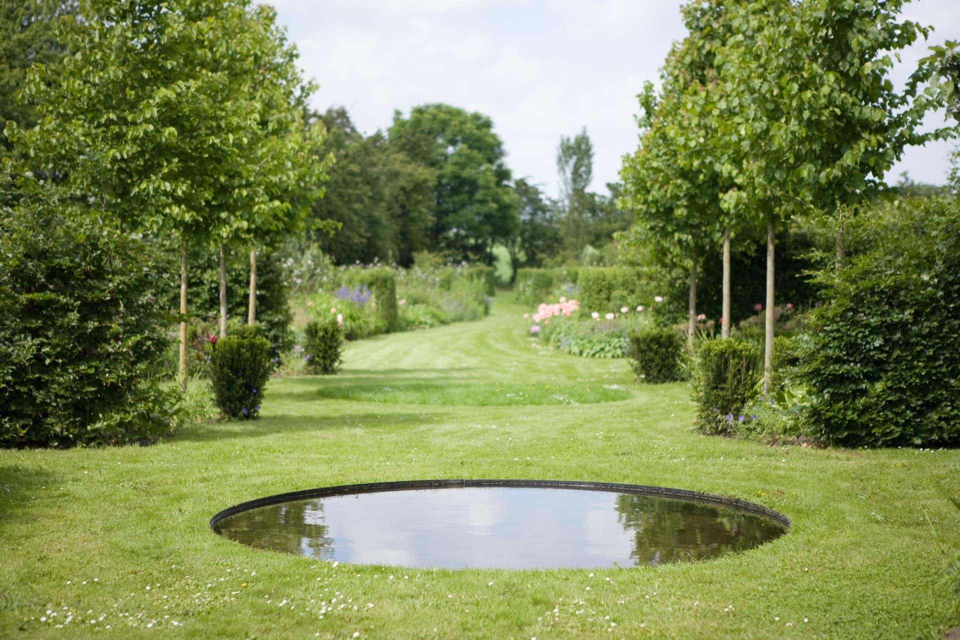 Den cirkelformade dammen speglar och drar ned himlen i dammen. Utsikt mot de böljande stora perennrabatterna.