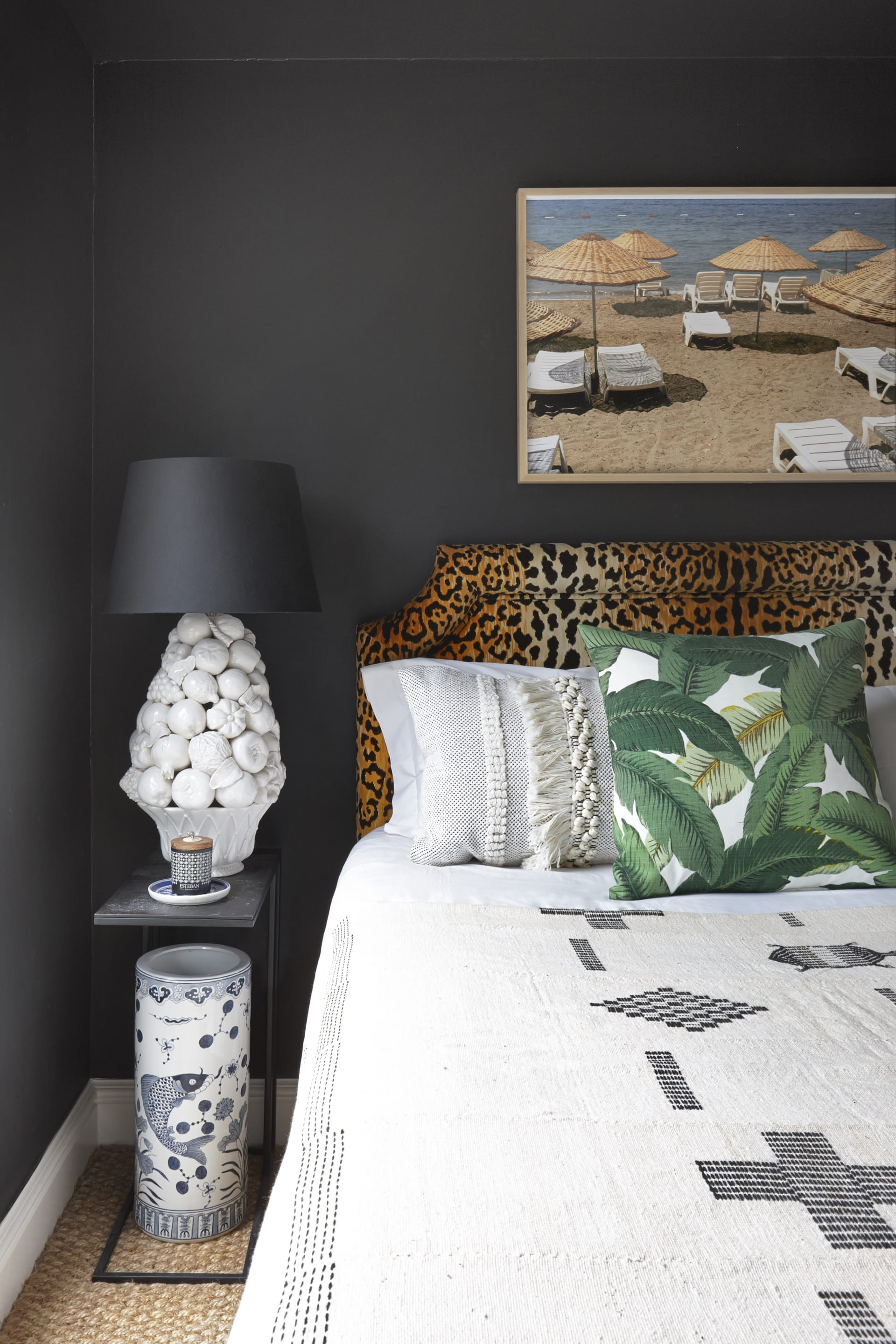 In the uniquely eclectic bedroom a framed photograph by Jen Jengo hangs on matt black wallsabove a leopard print headboard.© Micky Hoyle