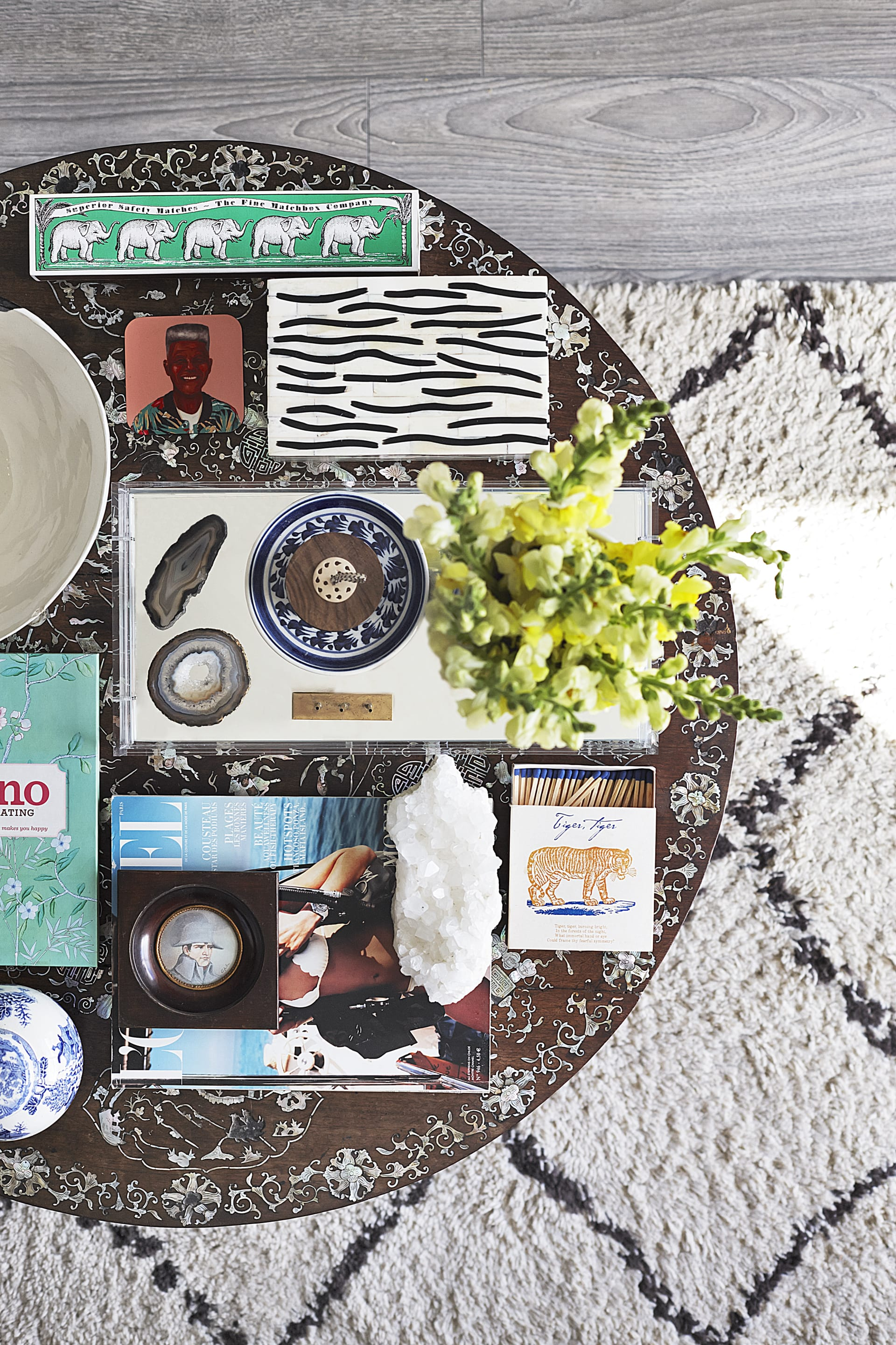 An inherited antique coffee table, handmade in Vietnam with mother of pearl inlay supports a visually impactful mix of beloved objects and collectibles. © Micky Hoyle
