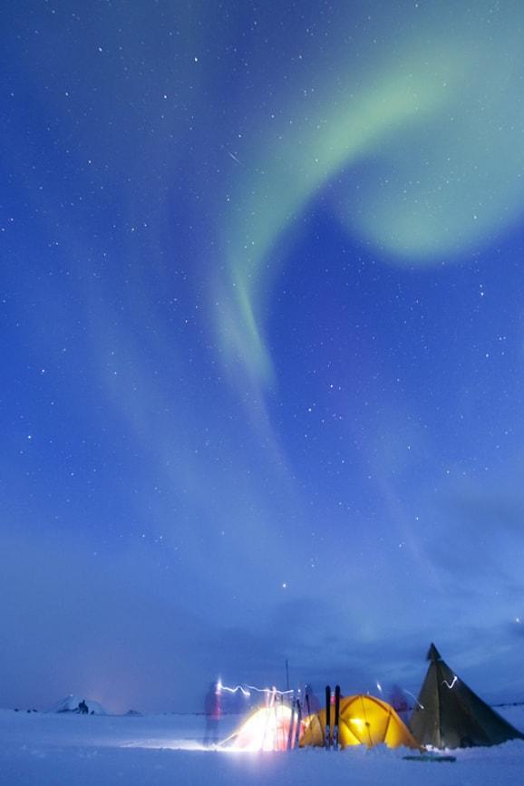Ett lekande norrsken över tältlägret.