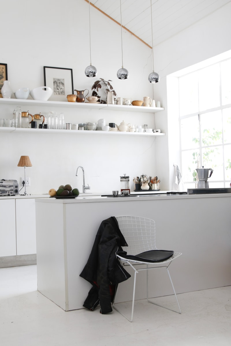 Thefunctional white kitchen is a practical space with open shelves for crockery and glassware, here again accents of black are introducedin the pictures and tableware items.