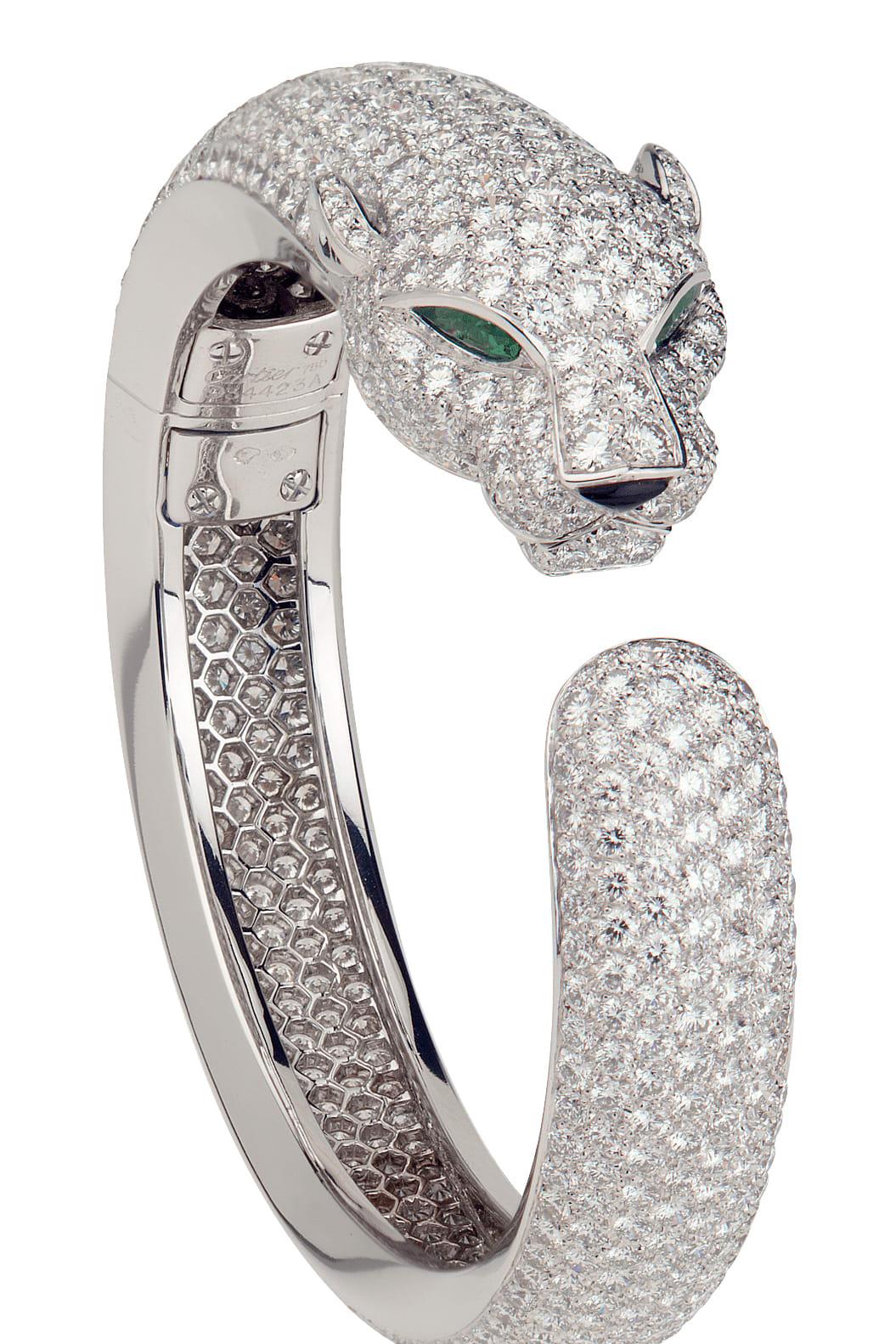 Panthére ring i vitt guld med briljantslipade diamanter samt smaragder och onyx. © Cartier