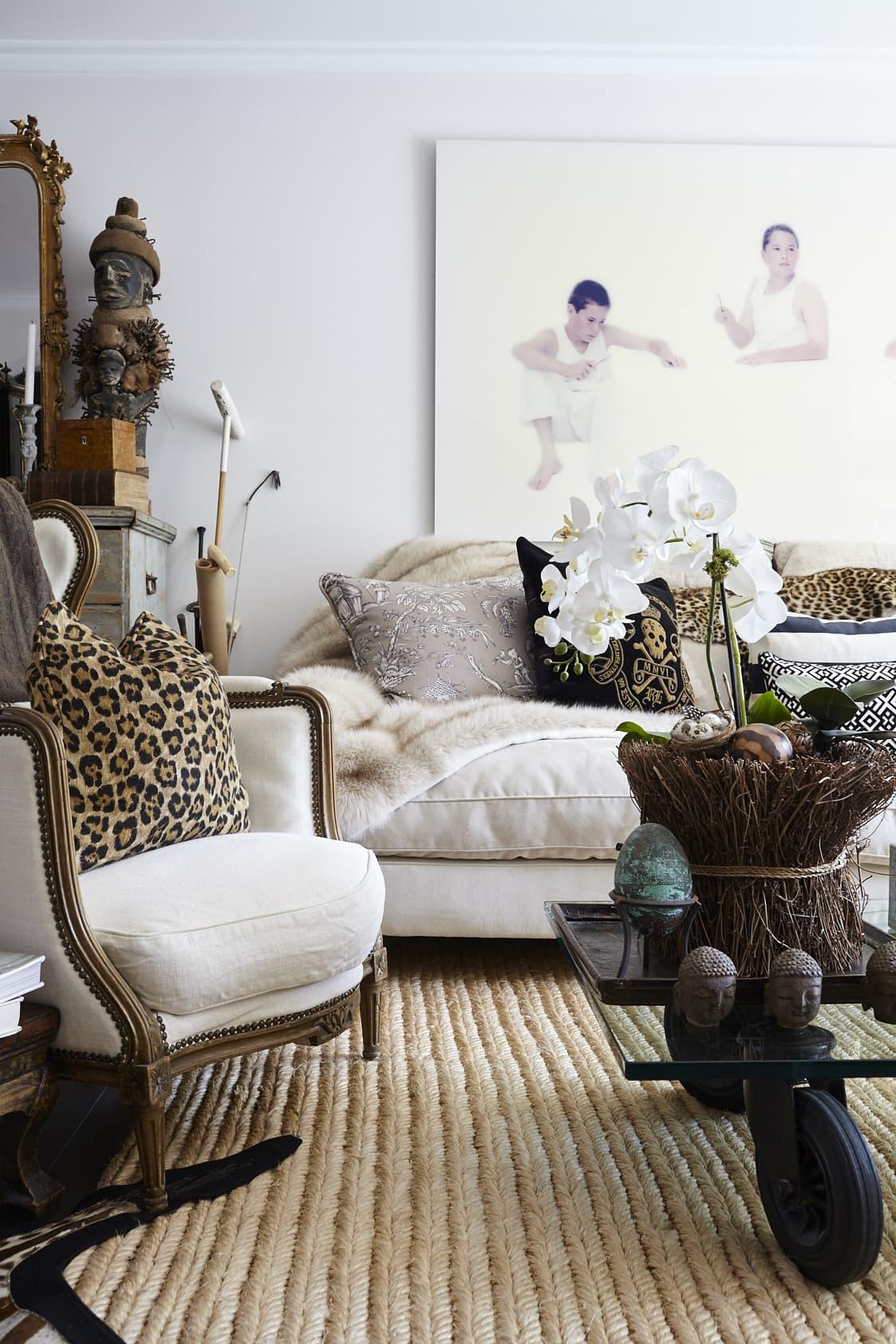 Anna är inte rädd för stilblandningar och mixar äldre möbler med moderna. 1700-talsfåtöljen är inropad på Bukowskis. Den afrikanska masken är från ett galleri i Göteborg och mellan byrån och soffan står några poloklubbor som en rolig detalj.