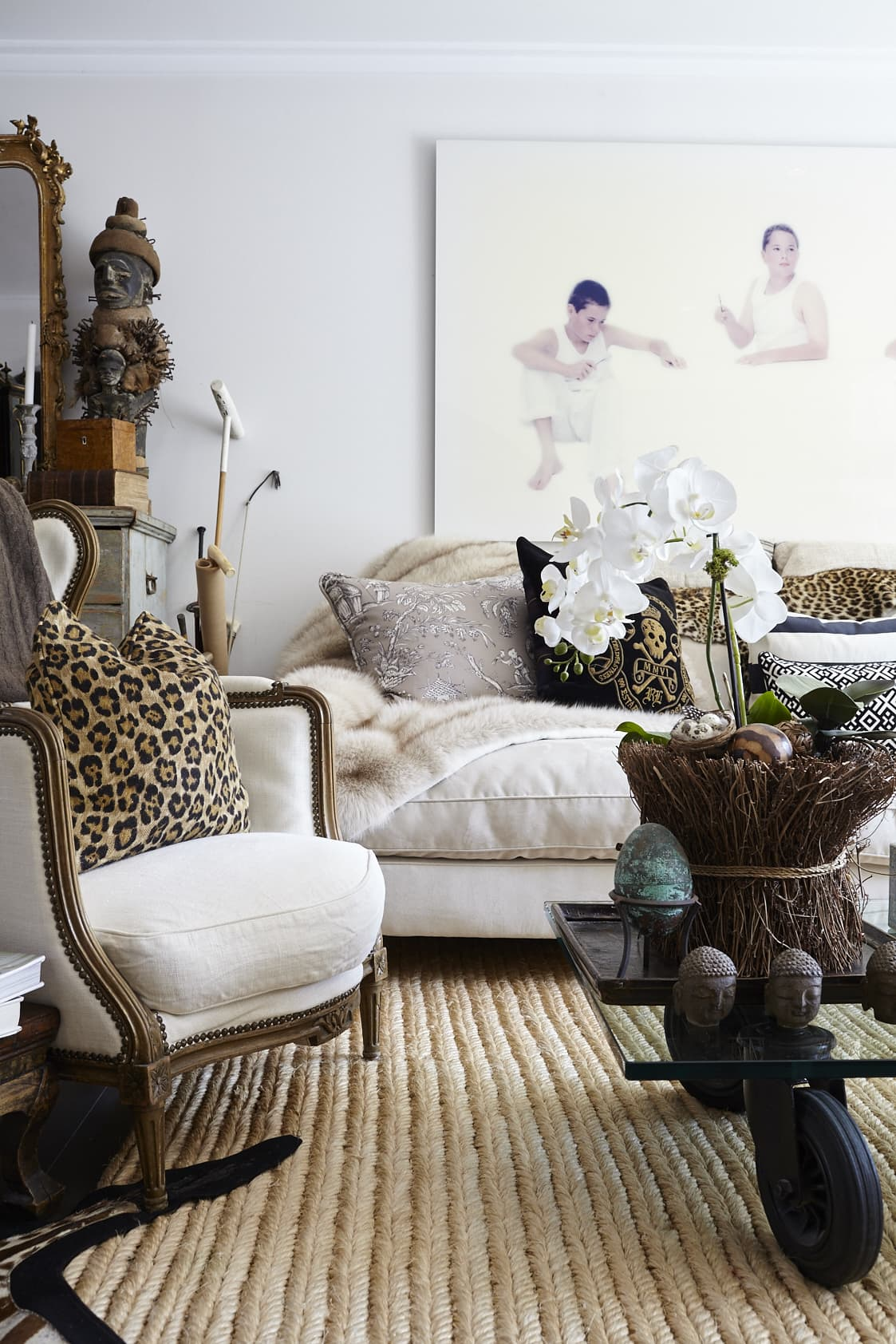 Mixing old furniture with new, Anna is not shying away from combining styles. The 18th-century chair is from Bukowskis. The African mask is from a gallery in Gothenburg and between the dresser and the couch are some polo sticks as a fun detail.