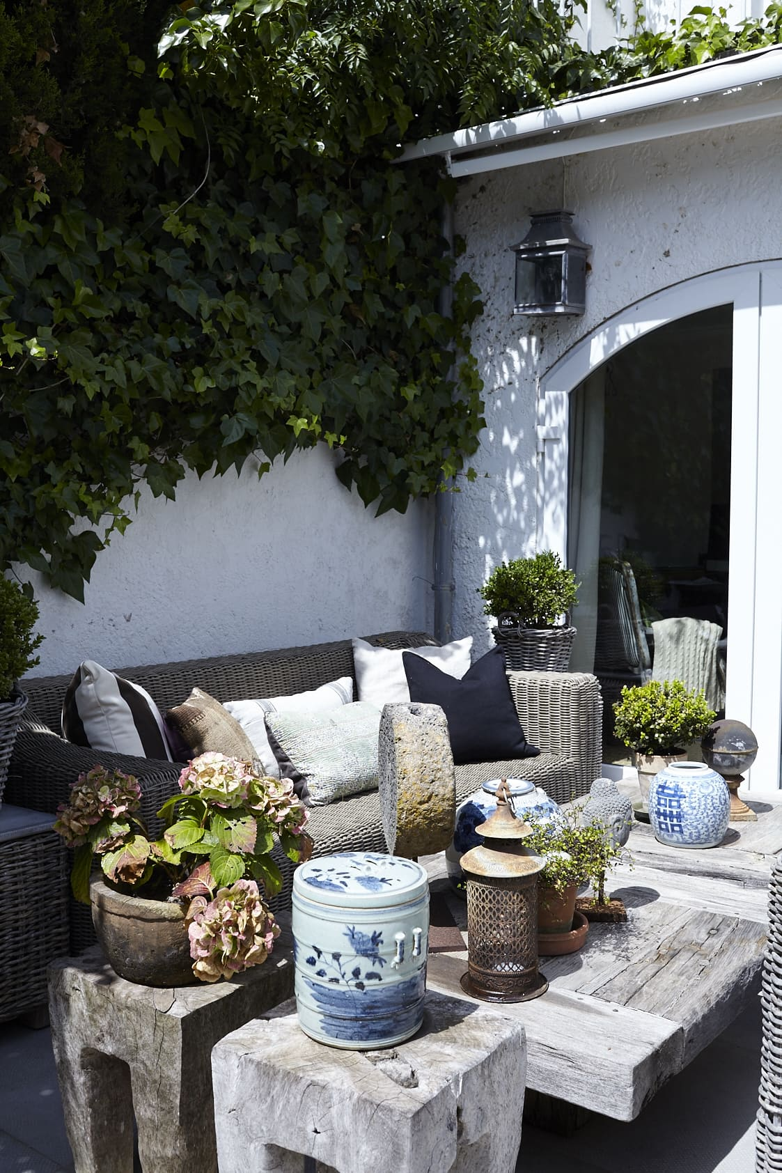 Thanks to details like blue and white porcelain, lanterns and statuettes, this courtyard feels like an outside living room. The wicker sofa and wooden tables were bought in Belgium.