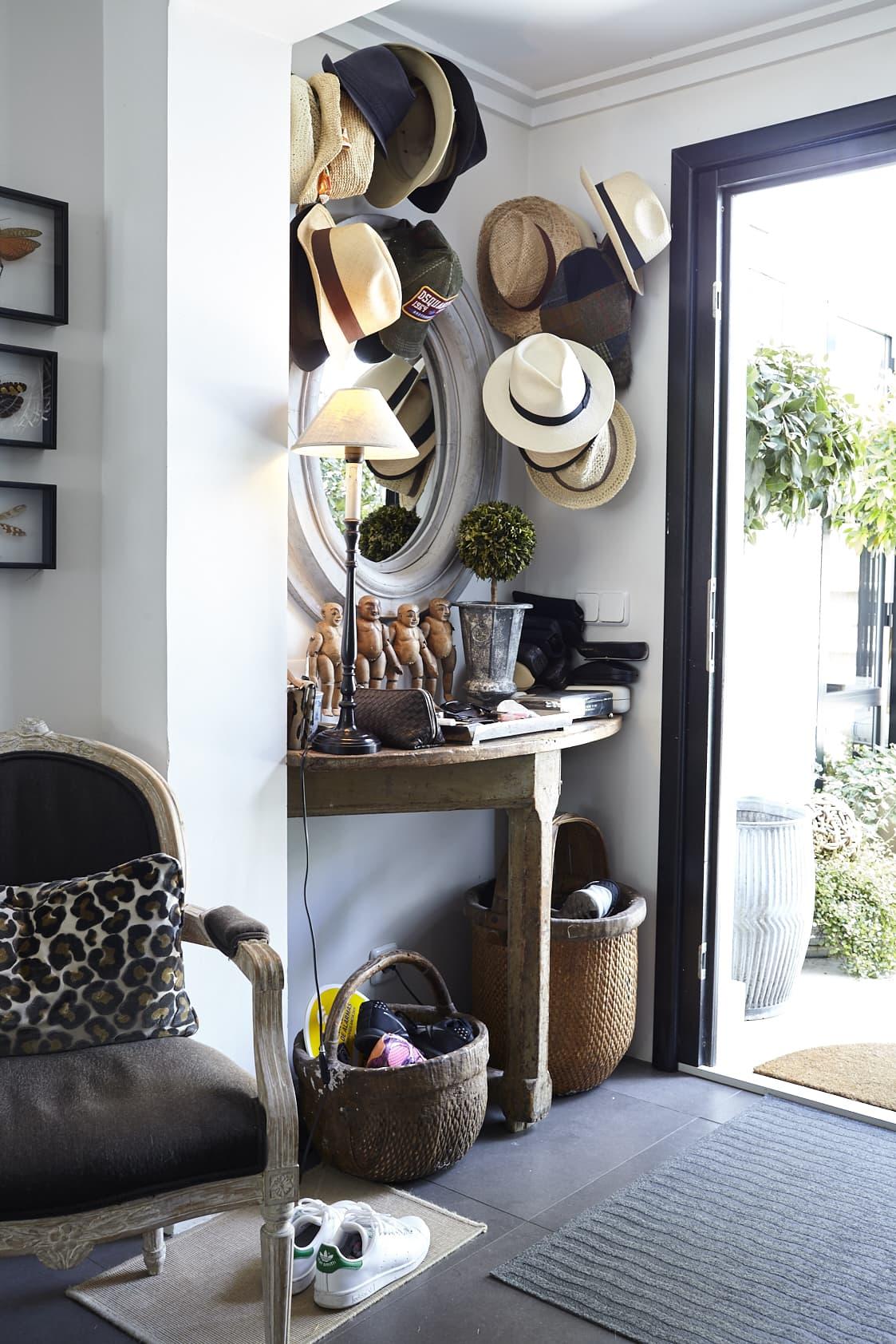 Hallen välkomnar med ett gammalt träbord som Anna ropat in på auktion. Hattsamlingen har hamnat på väggen och det blir lika dekorativt som praktiskt.