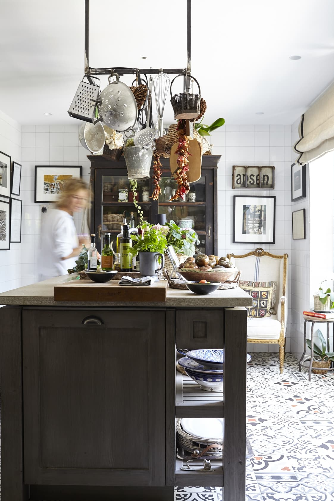 In the lower part of the kitchen, which used to be a garage, the kitchen island plays the main role. It was built by carpenters in Mallorca and features a sink as well as room for both cooking and storage. The Moroccan ceramic tiles on the floor and the classic white tiles leading all the way up to the ceiling are reminiscent of a tavern.