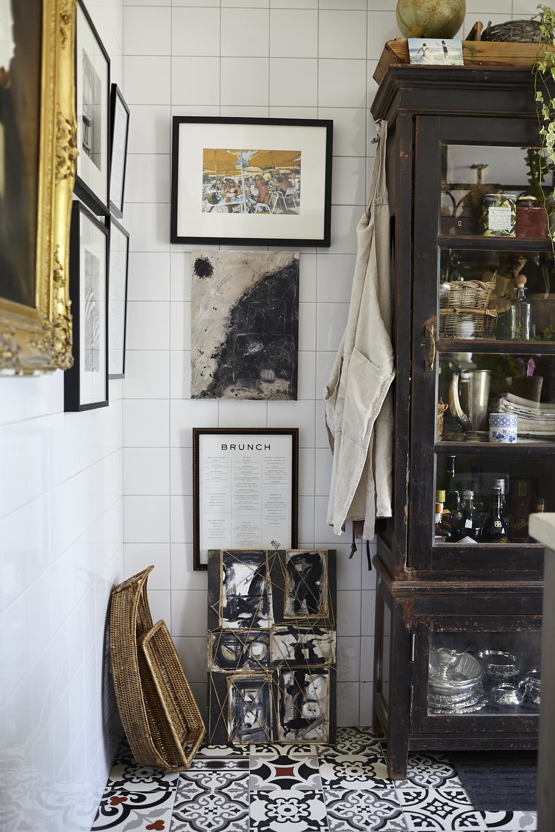 I en kökets ena hörn har Anna ramat in några krogmenyer som hon mixar med fotografier och ett porträtt i en praktfull guldram. Det svarta skåpet kommer från Holland.