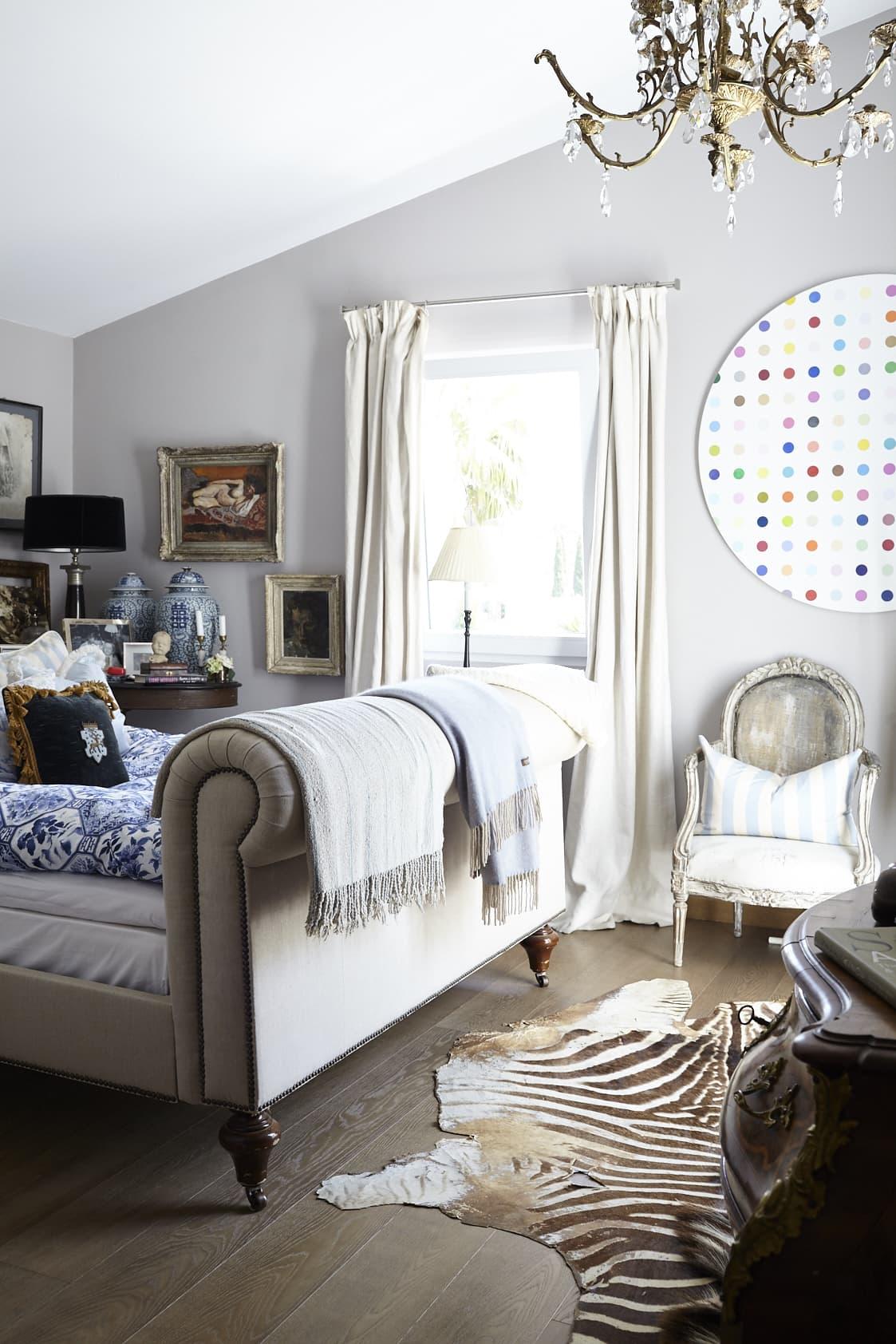 Annas sovrum ligger en trappa upp mot trädgården och har utgång till en egen liten terrass. En färgpalett av beige, ljusgrått, ljusblått och blått ger harmoni. Sängen är från Ralph Lauren och takkronan är ett loppisfynd.