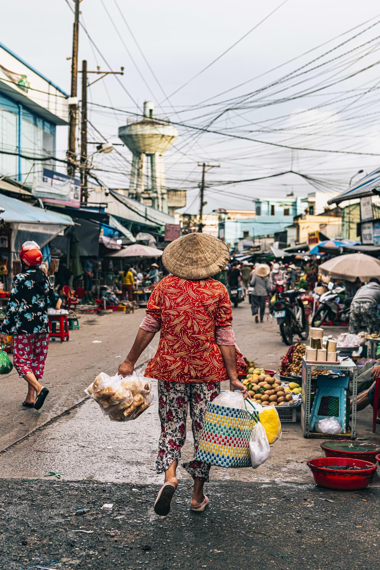 A woman walking downNguyen Trung Truc Street, carrying her morning shopping.