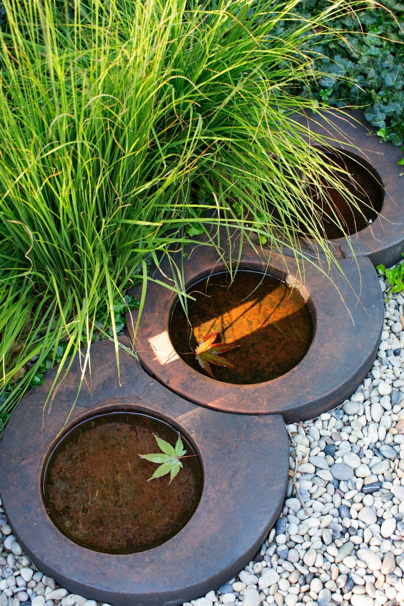 Vattenbadet från Löddeköpinge plantskola är placerat intill trädäcket, gräset blåtåtel, Molinia caerulea `Moorhexe` når en höjd av 40 cm.