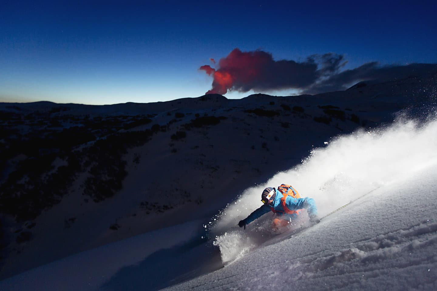 Oscar Hübinette enjoying some evening skiing with the red volcano plume of Tolbachik on the horizon.