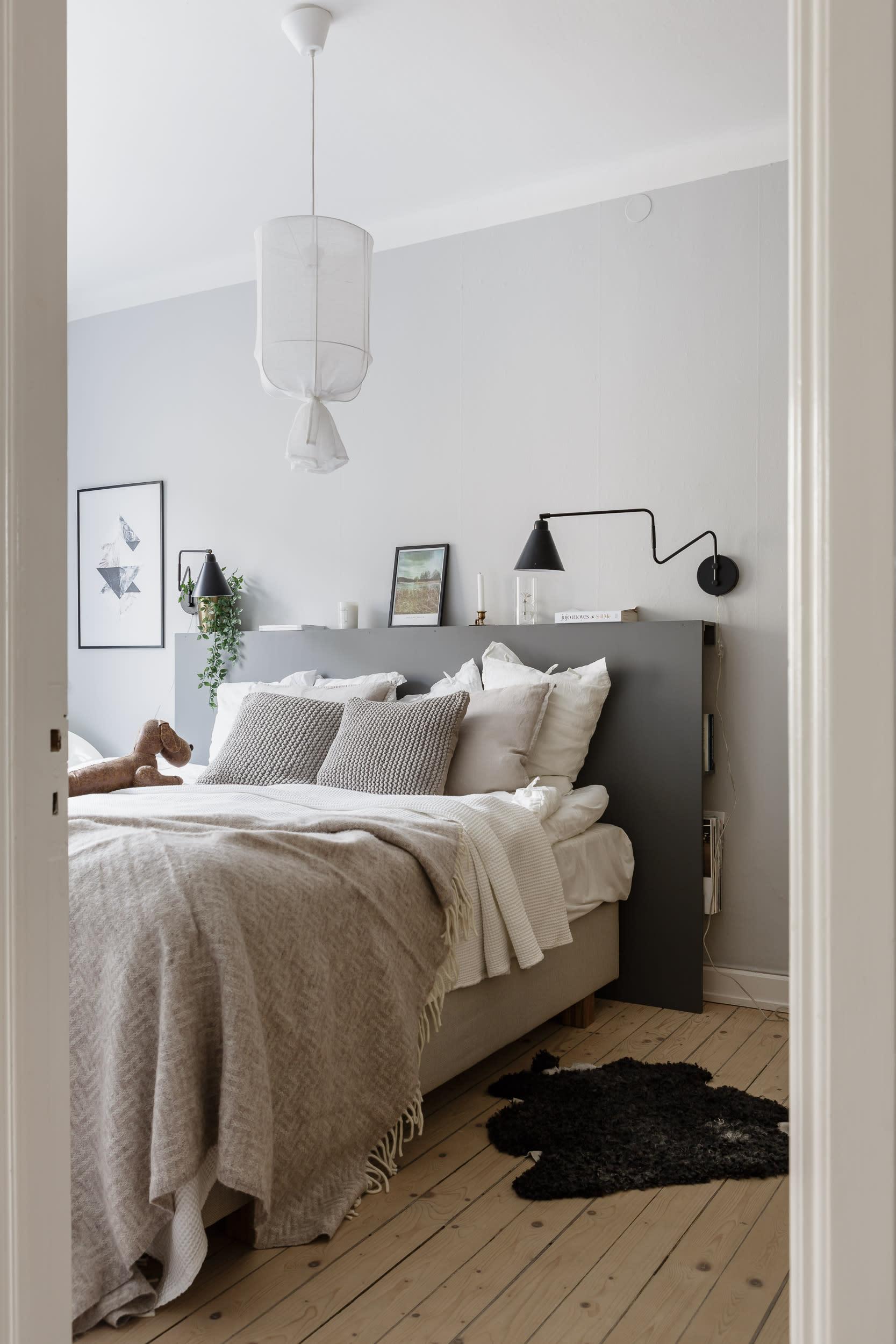 Charlotte har själv tillverkat sänggaveln avav tavellister från Ikea och en stor mdf-skiva som hon målat grå.