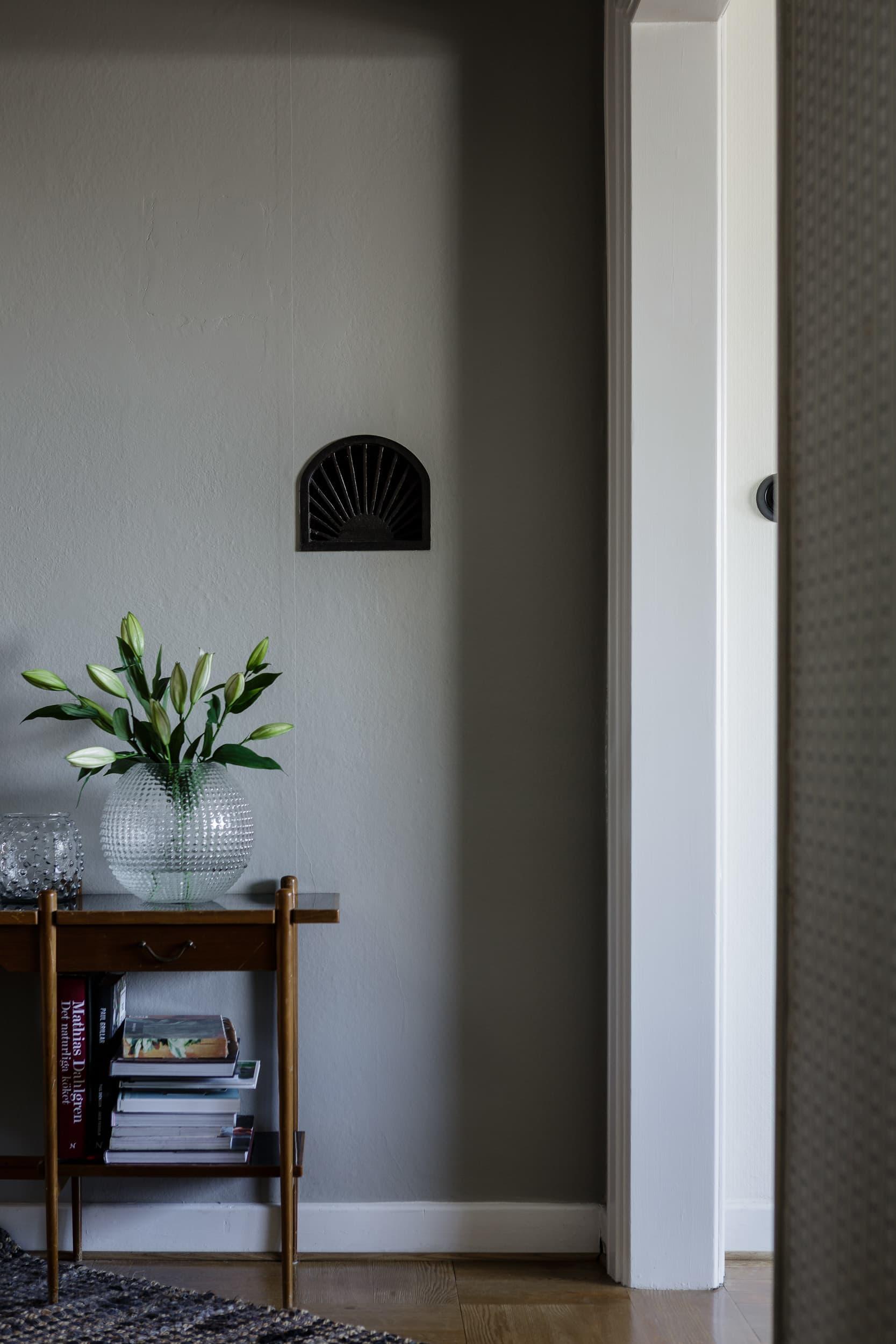 I hallväggen syns ännu ett spår av husets original. Här har familjen låtit en gamla ventilationslucka vara intakt.