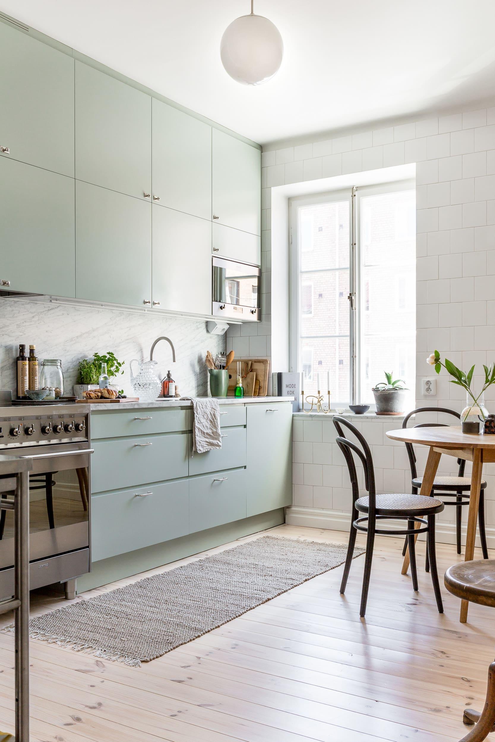 Köket är något alldeles extra med sina helkaklade väggar, marmorskivor och mjukt gröna luckor.Kök från Kolmårdskök och beslag från Byggfabriken.