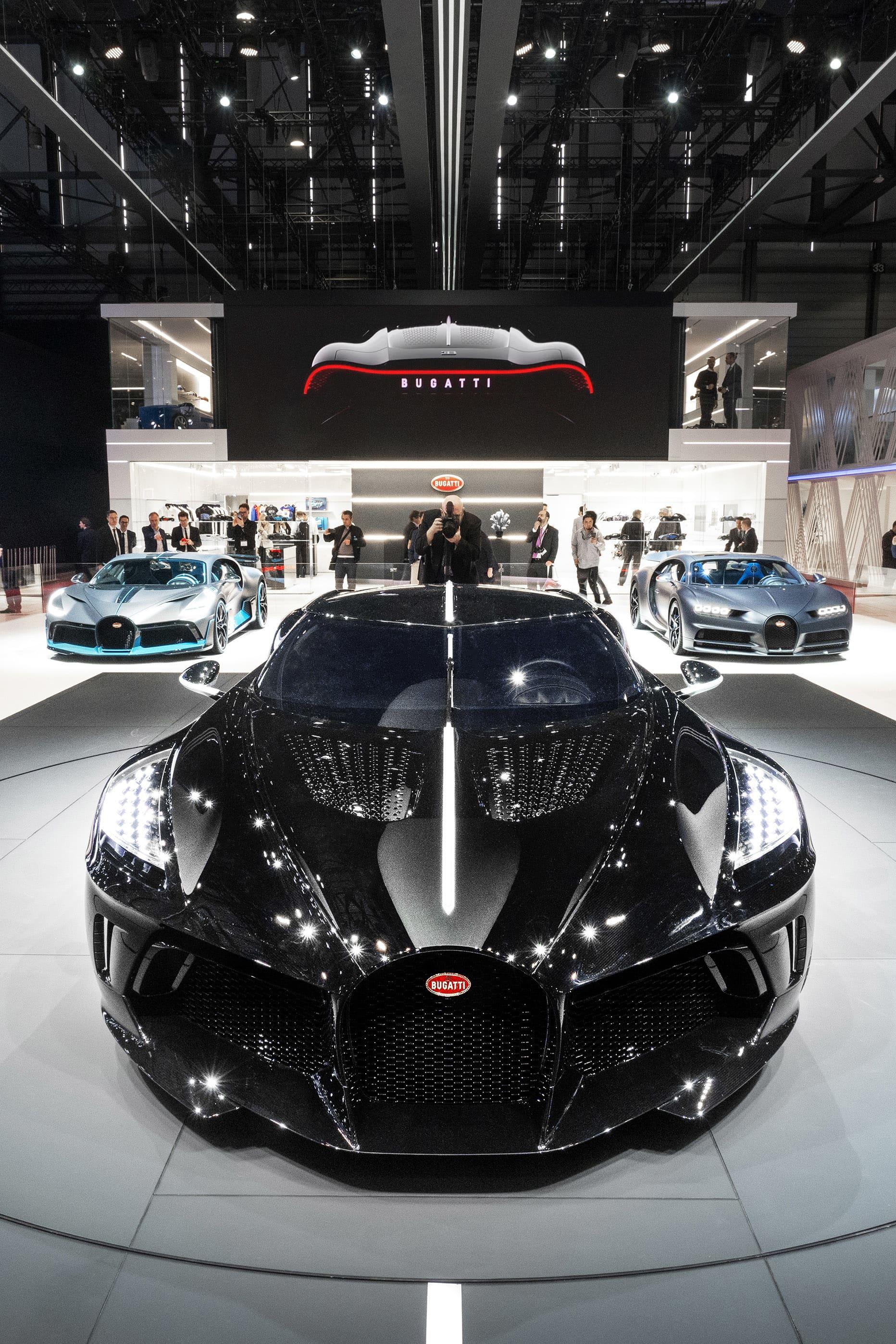 """Bugatti La Voiture Noire, Diva och """"110 ans Bugatti"""" - mässans dyrgripar.  Mässans absolut dyraste bilar var kanske inte så förvånande från Bugatti. Med endast tre bilar i sin monter var troligen det sammanlagda värdet mer än resten av samtliga märken de delade hall med. Mässans stjärna blev utan tvekan modellen La Voiture Noire """"Den svarta bilen"""". Endast ett ex kommer byggas och ryktet säger att det är den forna Volkswagengruppägaren Ferdinand Piëch som är personen som beställt bilen. Prislappen på denna unika bil som inspirerats av den klassiska Bugatti modellen 57 SC Atlantic landar på 16,7 miljoner euro innan skatt. Det var dock inte den enda bilen i montern värd att nämna eftersom man även visade upp Divo samt Chiron Sport """"110 ans Bugatti"""". Den förstnämnda med ett tillverkningstal om 40 ex och en prislapp på 5 miljoner euro och den andra i endast 20 exemplar och till ett pris på 2,65 miljoner euro."""
