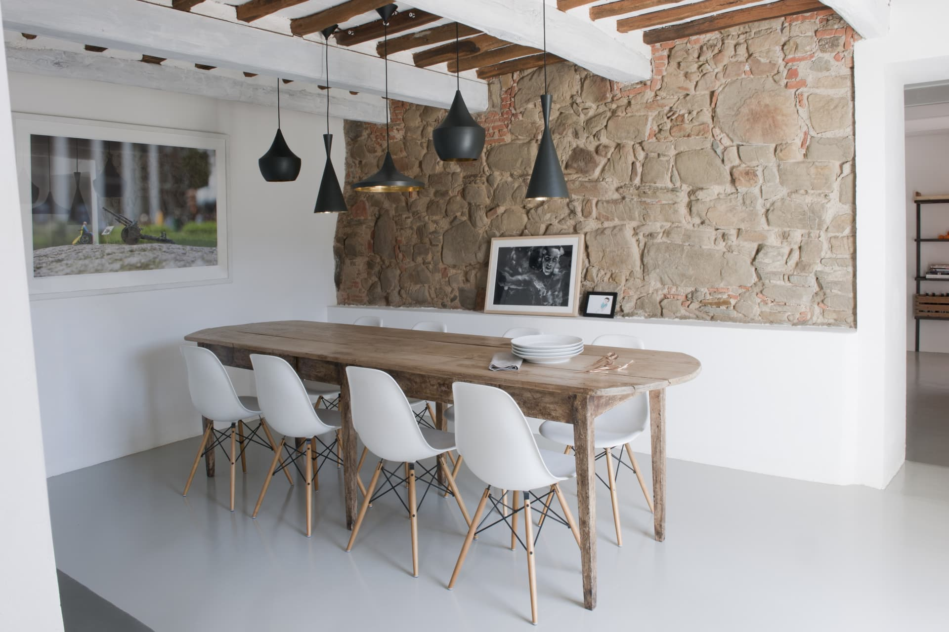 The dining room. The long wooden table is from Barthel, the chairs are from Eames, the lamps by Tom Dixon.