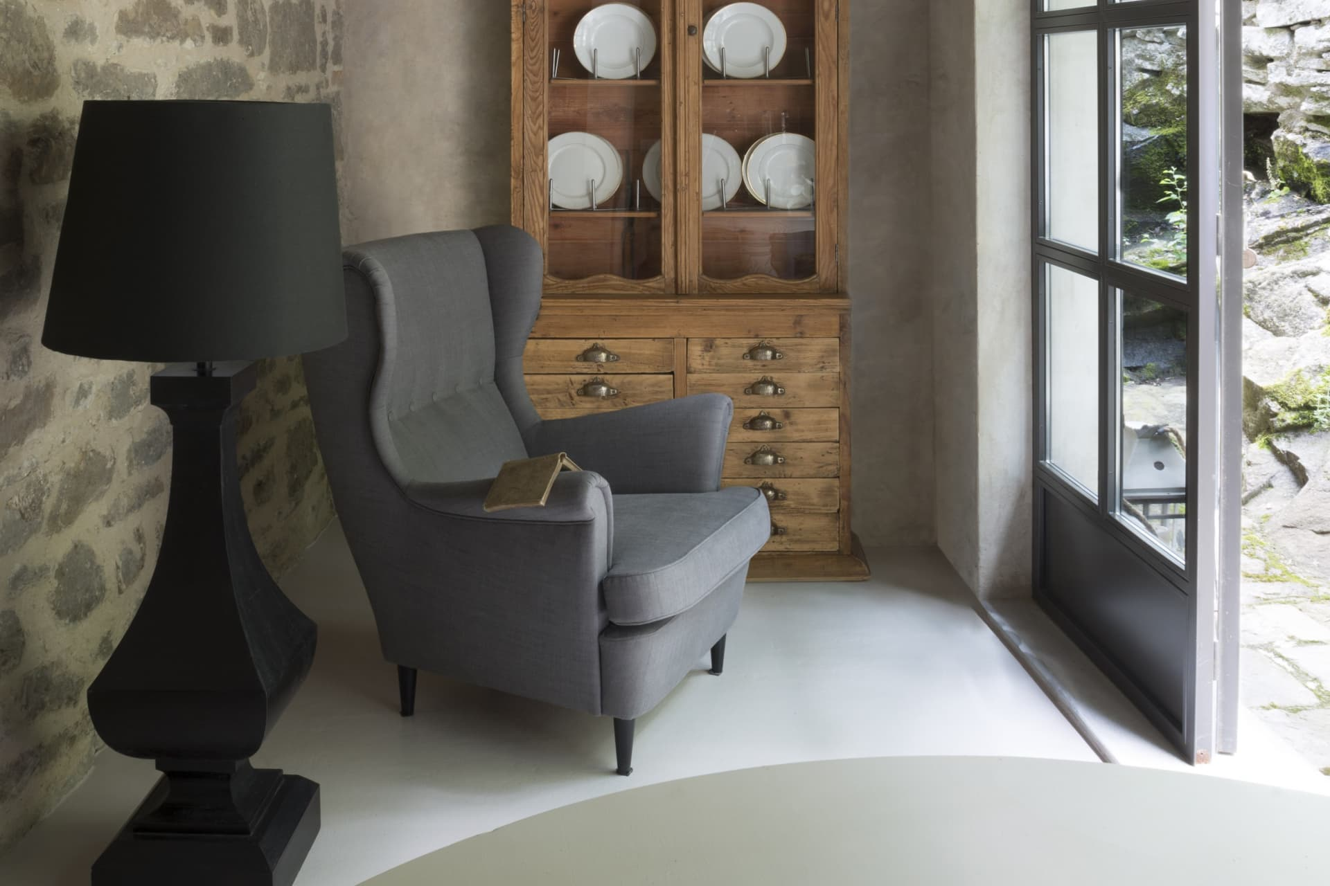 The corner of the limonaia, with an old pharmacy cabinet used as a sideboard. The gray fabric armchair is of local craftsmanship. The floor is resin-treated.