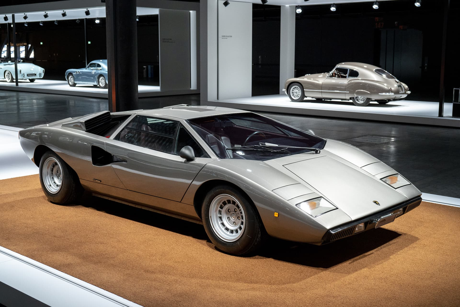 "This masterpiece and perhaps the world's most famous iconic car is undoubtedly designer Marcello Gandini's Lamborghini Countach. The model was first shown at Geneva's car show in 1971. The name arose when one of the craftsmen at the factory spontaneously exclaimed contacc"" when he first saw the car. ""Contacc"" is Piedemonte dialect and can be loosely translated into ""wow"". In 1974, the finished car rolled out from the factory and could reach a speed of 300 kilometers per hour even back then thanks to its shape and the powerful V12 engine."