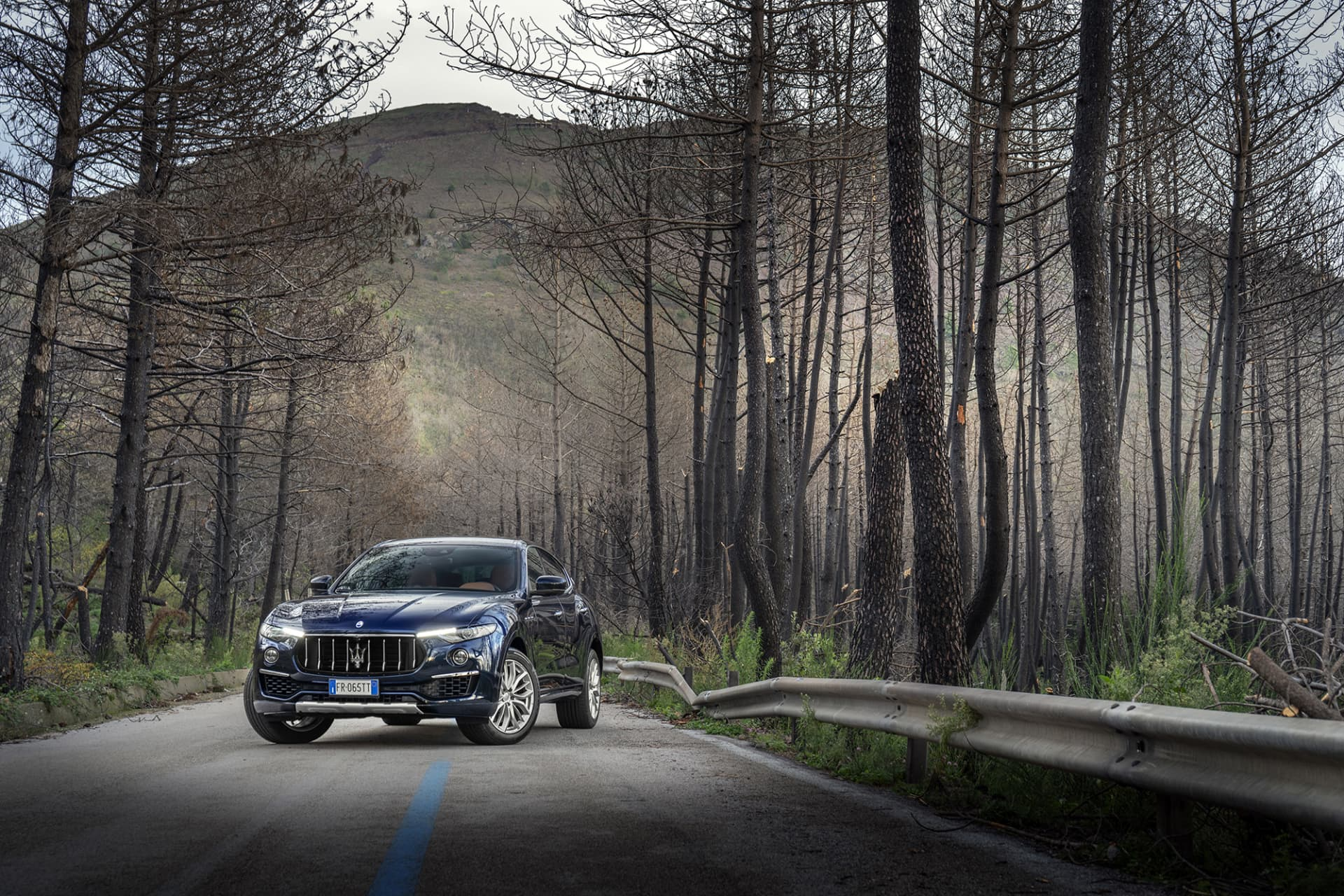 The Levante S stands out with an aggressive grill and the classic trident in the middle. Along the sides are burnt out trees and in the background the volcano Vesuvius.